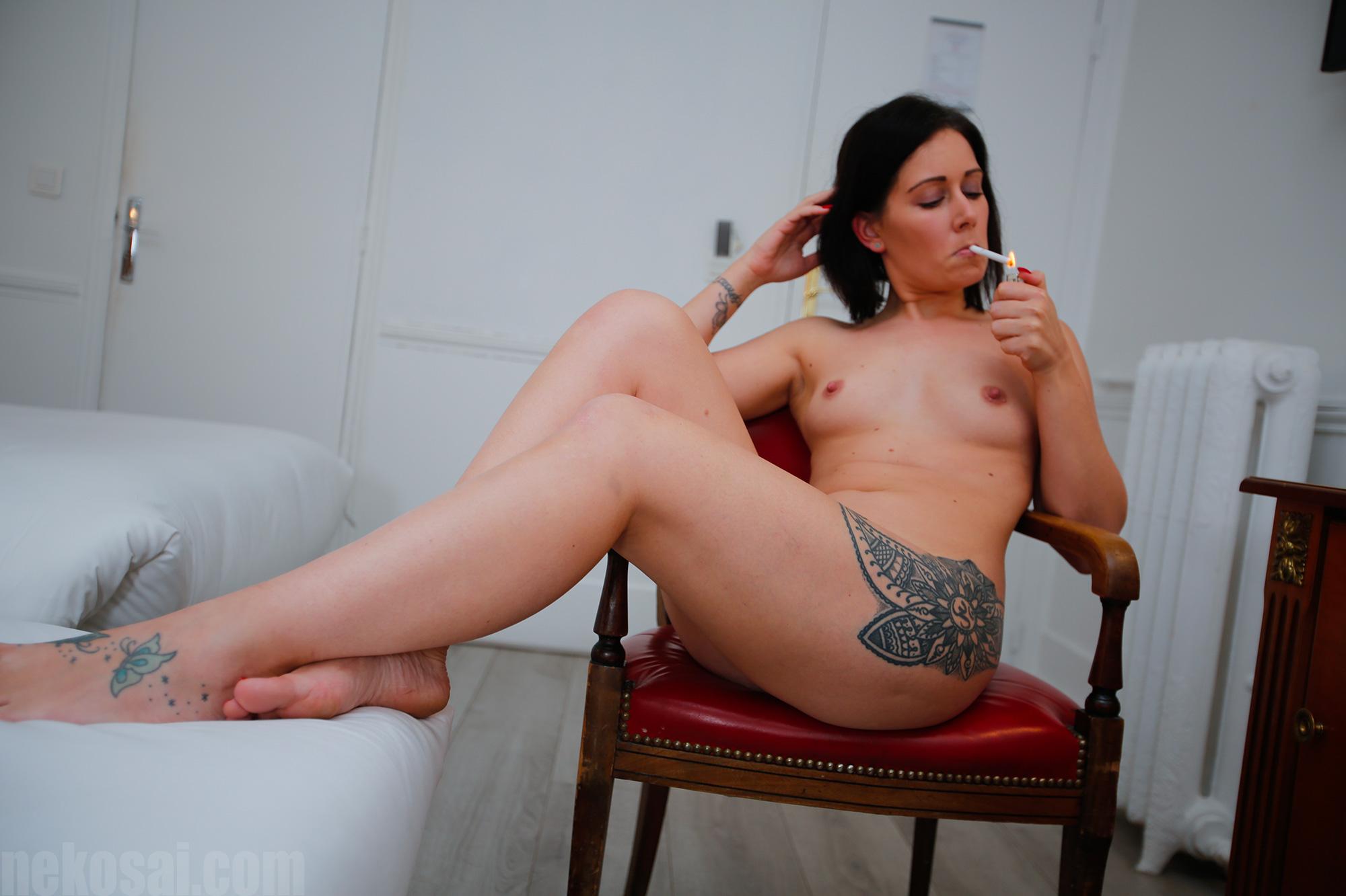 Une femme tatouée nue fume une cigarette