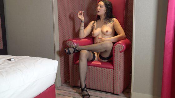 Une jeune femme tatouée, nue, fume une cigarette